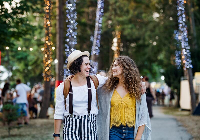Portrait of two young women friends at summer festival, walking. royalty free stock images