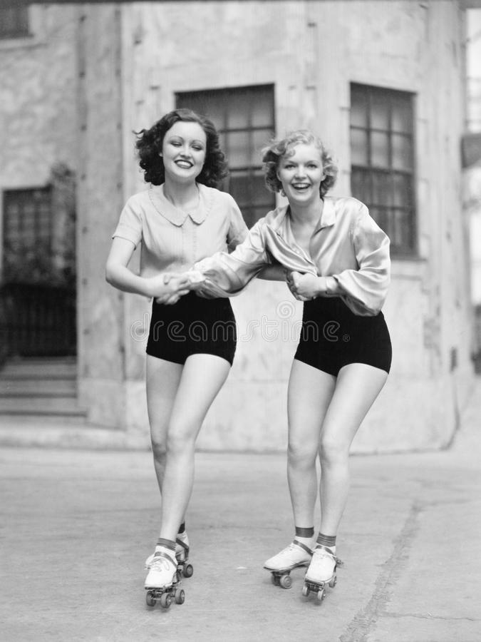 Portrait of two young women with roller blades skating on the road and smiling royalty free stock photo