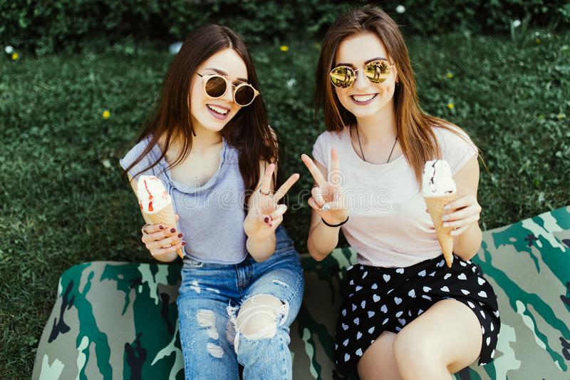 Portrait of two young women standing together eating ice creamn with peace gesture sitting on the grass in city street. royalty free stock photography
