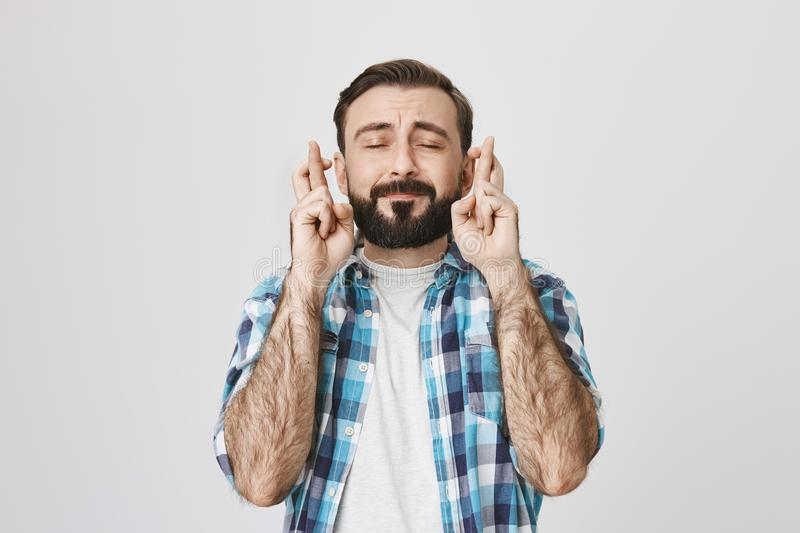 Portrait of typical adult european man with beard and moustache in checked shirt, crossing fingers and expressing royalty free stock images