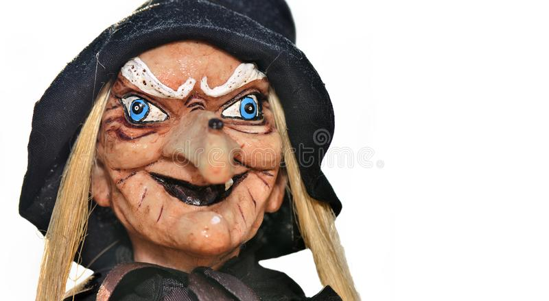 Portrait of an ugly witch doll with balck hat. On white background royalty free stock photography