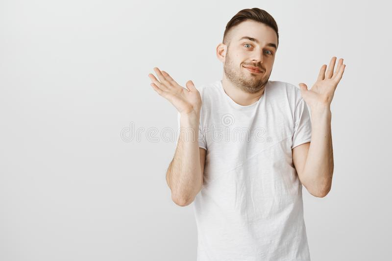 Portrait of unaware careless and indifferent handsome male student in white t-shirt with beard and moustache raising. Palms near shoulders while shrugging being royalty free stock photography