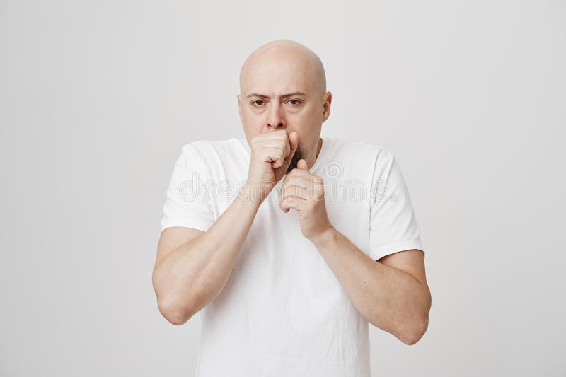 Portrait of unhappy bald bearded caucasian man holding fist near mouth as if wanting to throw up or coughing, being sick stock photography