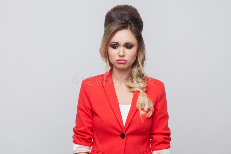 Portrait of unhappy beautiful business lady with hairstyle and makeup in red fancy blazer, standing and looking down with sad eyes. Indoor studio shot stock photography