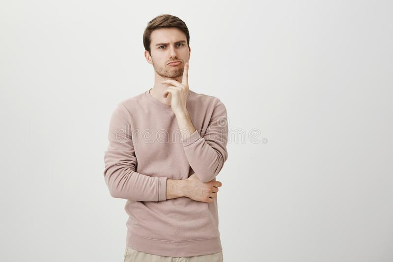 Portrait of unhappy determined european male with bristle touching chin while thinking and looking with serious and. Worried look at camera, standing against stock images