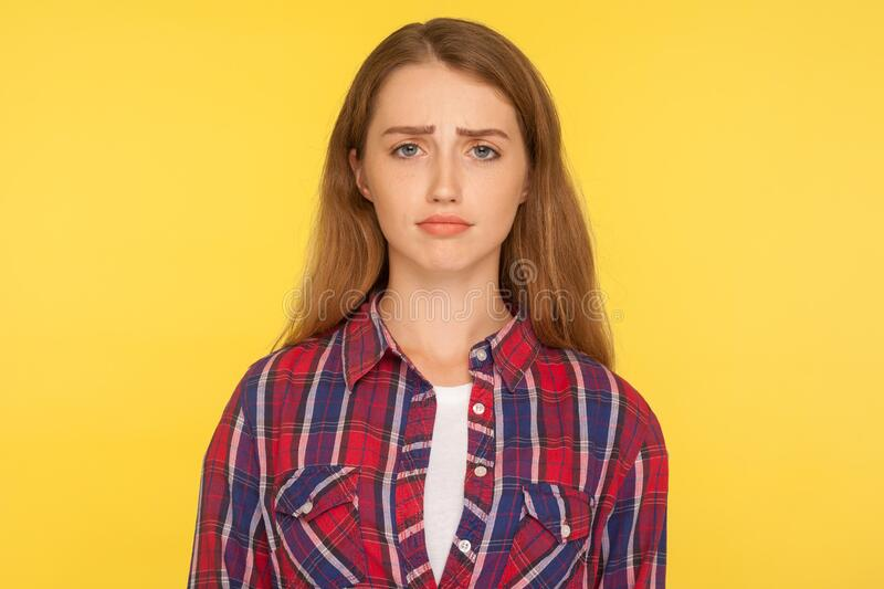 Portrait of unhappy ginger girl in checkered shirt frowning and looking at camera with upset dismal expression. Feeling insulted, resentful facial emotion royalty free stock image