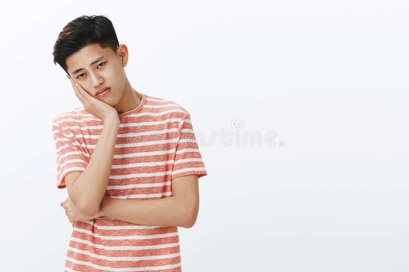 Portrait of unhappy lonely and sad young bored asian guy leaning head on palm looking with upset indifferent gaze at stock photos