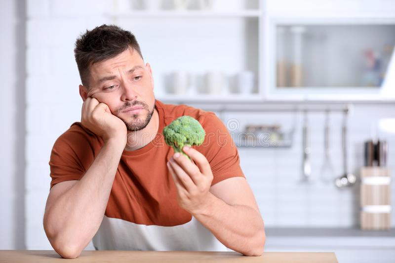 Portrait of unhappy man with broccoli at table stock photography