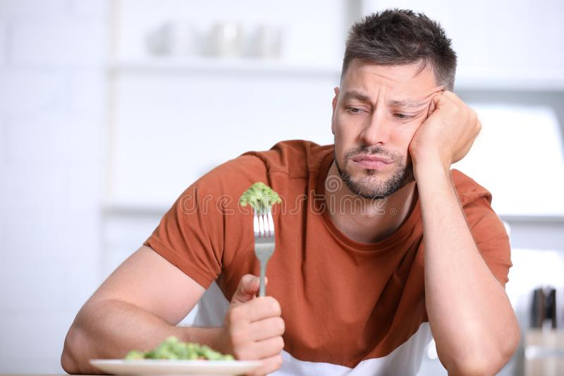 Portrait of unhappy man eating broccoli salad royalty free stock photography