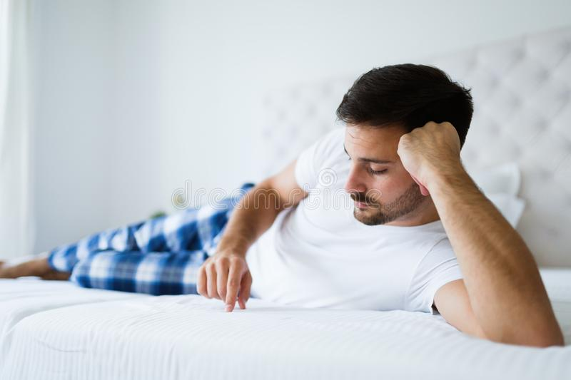 Portrait of unhappy man lying on bed. Portrait of young unhappy man lying on bed royalty free stock photo
