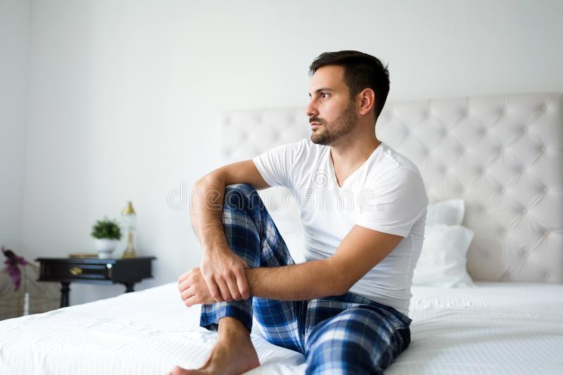 Portrait of unhappy man sitting on bed. Portrait of young unhappy man sitting on bed royalty free stock photography