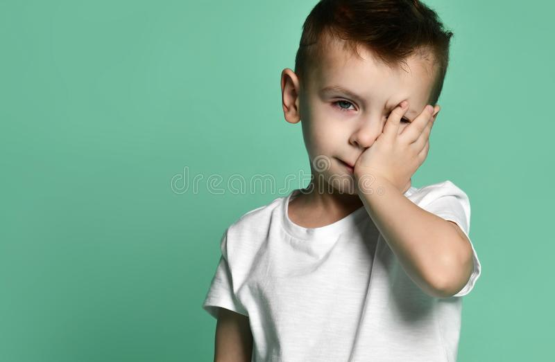 Portrait of unhappy sad bored kid boy leaning head on palm looking with upset royalty free stock photos