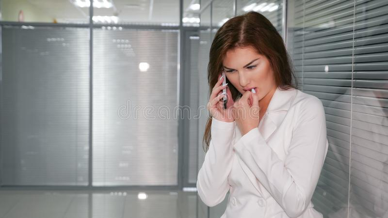 Portrait of unhappy young businesswoman speaking on phone in office royalty free stock images