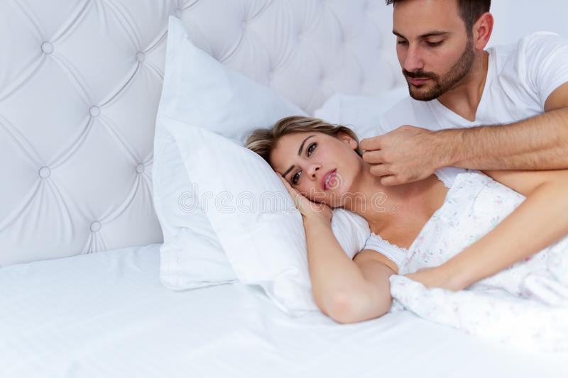 Portrait of unhappy young couple in bedroom. Portrait of unhappy young couple having problems in bedroom royalty free stock photos