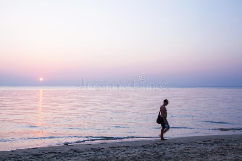 Portrait of unidentified bare-chested men with tote bag walking barefoot on a beach at sunset. Blurred motion. Long exposure. royalty free stock photos