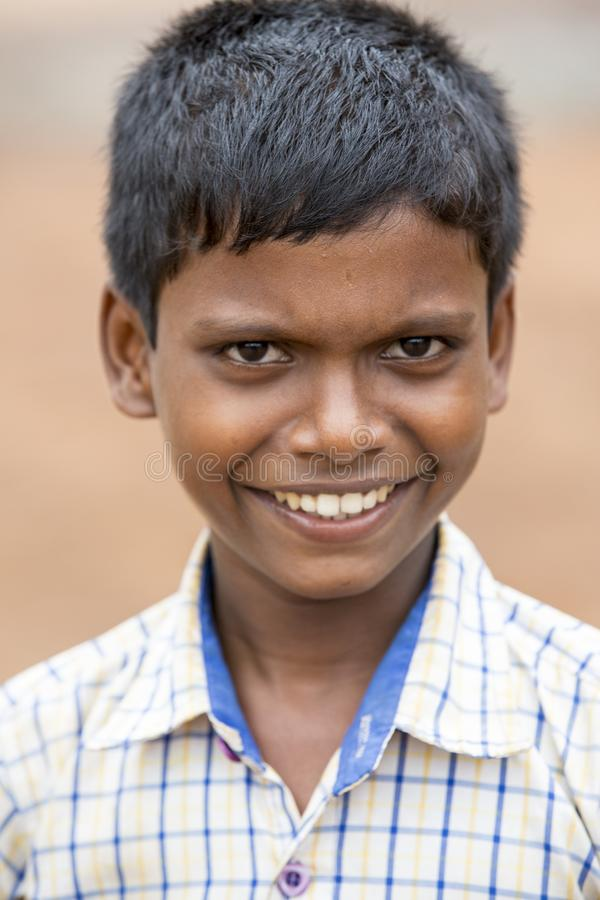 Portrait of unidentified Indian poor kid boy is smiling outddor in the street. PONDICHERY, PUDUCHERRY, TAMIL NADU, INDIA - SEPTEMBER CIRCA, 2017. Portrait of stock image