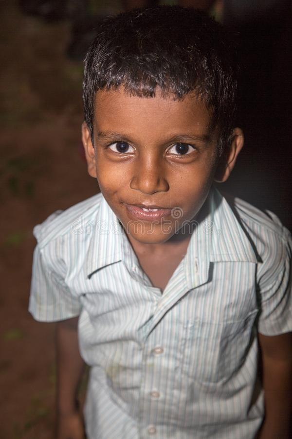 Portrait of unidentified Indian poor kid boy is smiling outddor in the street. PONDICHERY, PUDUCHERRY, TAMIL NADU, INDIA - SEPTEMBER CIRCA, 2017. Portrait of royalty free stock photo