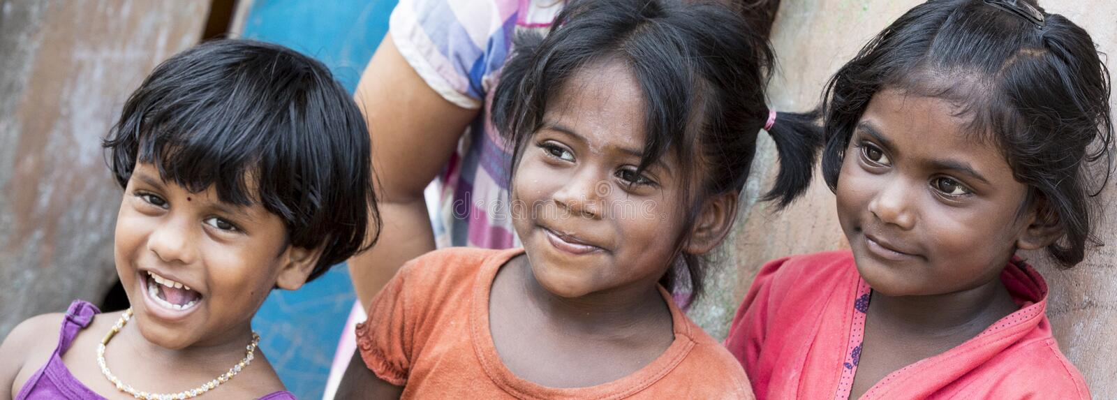 Portrait of 3 unidentified Indian poor kid girl child is smiling outddor in the street. PONDICHERY, PUDUCHERRY, TAMIL NADU, INDIA - SEPTEMBER CIRCA, 2017 stock images