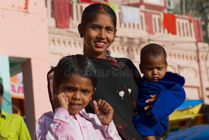 Portrait of an unidentified lady pilgrim with two kids at the bank of the Holy Ganges river in Varanasi, India. stock photo