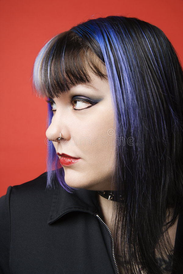Portrait of unique woman. Portrait of Caucasian woman with blue hair, tattoo, and spike collar looking to side against orange background stock photos