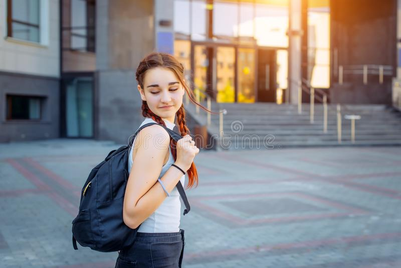 Portrait of University student, girl with backpack while going to college from street, teenager in campus. Education concept stock image