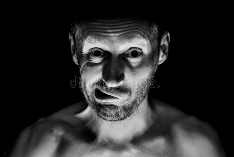 Portrait of unshaven adult caucasian man. He smiles like maniac and seems like madness. Black and white shot, low-key lighting. Isolated on black stock photos