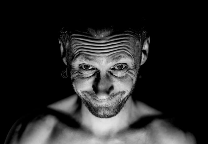 Portrait of unshaven adult caucasian man. He smiles like maniac and seems like madness. Black and white shot, low-key lighting. Isolated on black stock photo