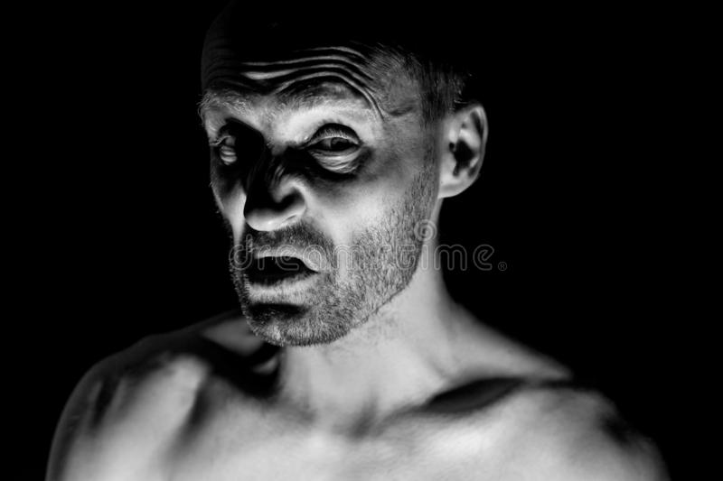 Portrait of unshaven adult caucasian man. He smiles like maniac and seems like madness. Black and white shot, low-key lighting. Isolated on black royalty free stock photography