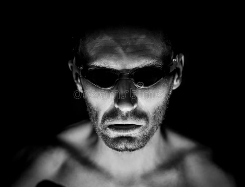 Portrait of unshaven adult caucasian man in swimming glasses. He smiles like maniac and seems like madness. Black and white shot,. Low-key lighting. Isolated on stock photography