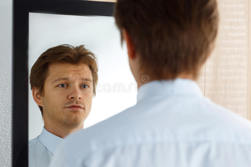 Portrait of unsure young businessman with unhappy face stock photography