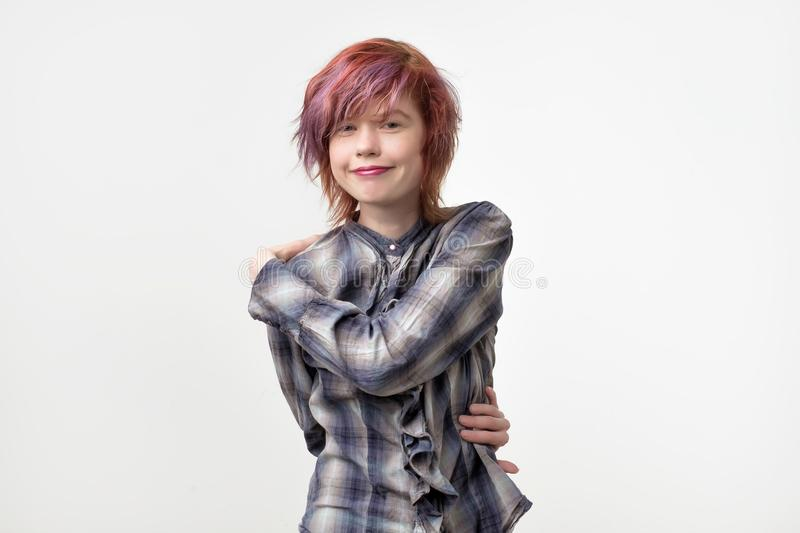 Portrait of unusual informal pretty woman with colorful hairstyle pretending like she is hugging herself. Being proud. stock photo
