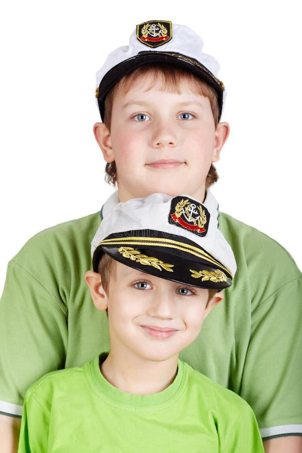 Portrait up of two boys in sea peak-cap