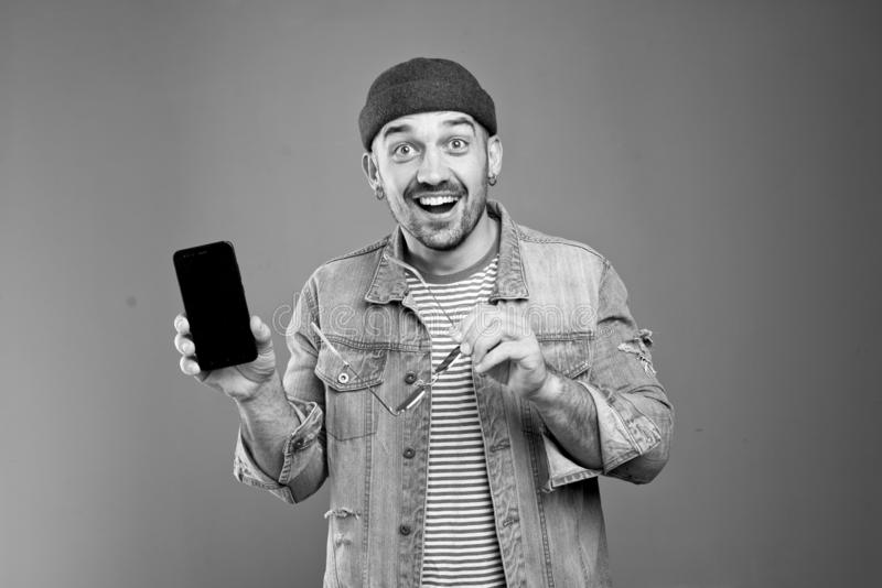Portrait of upbeat stylish man smiling broadly while showing his smartphone stock photography