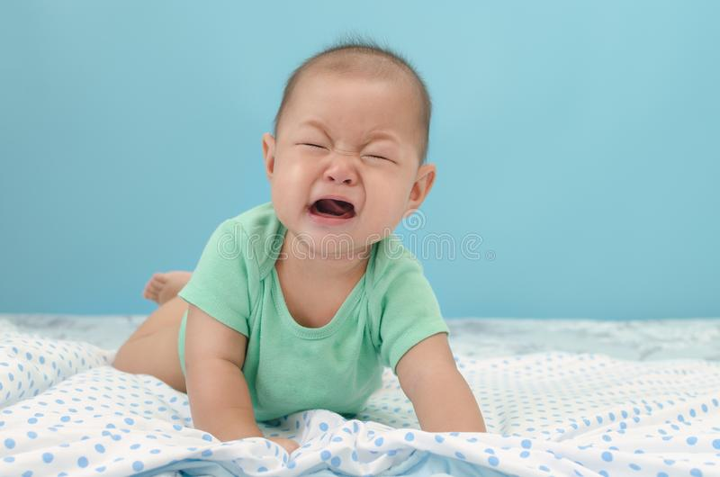 crying baby boy on bed royalty free stock photos