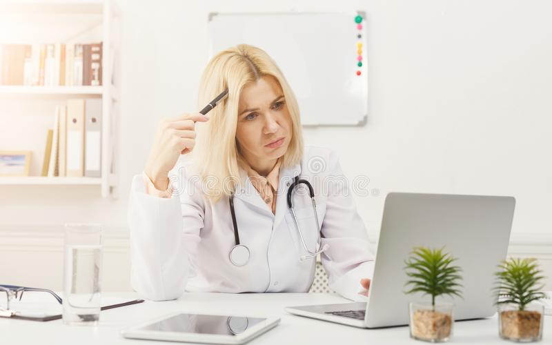 Portrait of upset doctor sitting at the desktop stock images