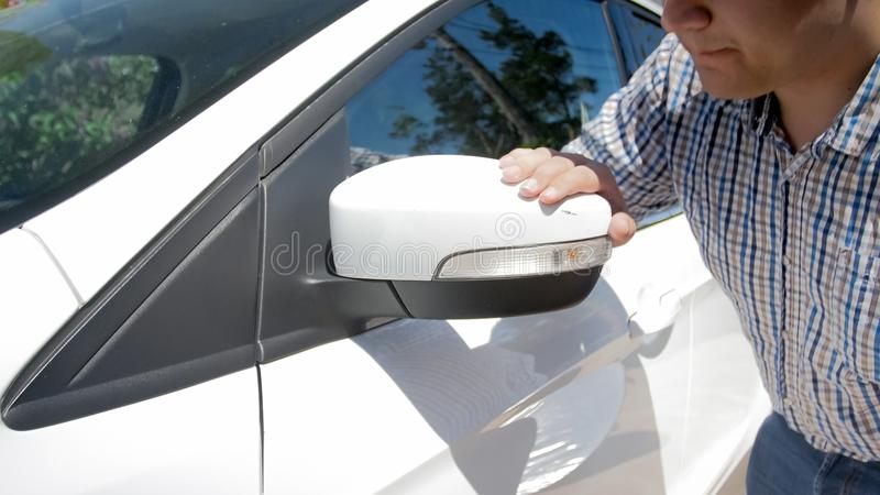 Portrait of upset male driver looking at paint scratch on car side mirror royalty free stock images