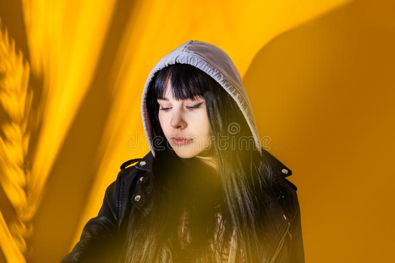 Portrait upset girl woman hood sunglasses background yellow sad grief sorrow brunette shadow sun light tropical leaves. Portrait of upset girl with hood on her royalty free stock image