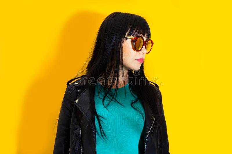 Portrait upset girl woman sunglasses background yellow sad grief sorrow brunette shadow sun light tropical leaves. Portrait of upset girl with red sunglasses stock photos