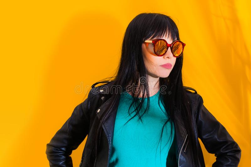 Portrait upset girl woman sunglasses background yellow sad grief sorrow brunette shadow sun light tropical leaves. Portrait of upset girl with red sunglasses royalty free stock photo