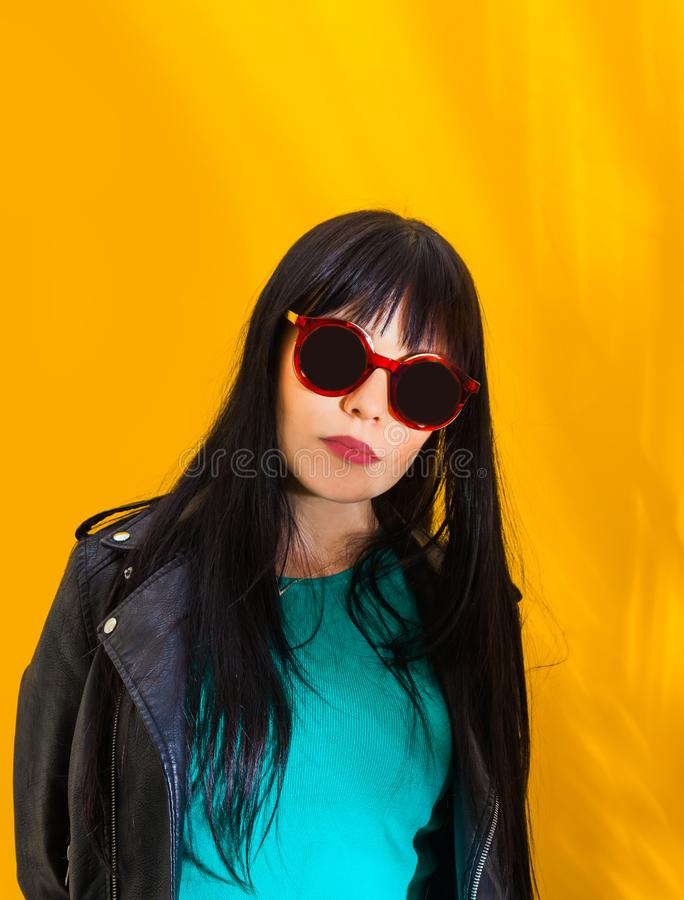 Portrait upset girl woman sunglasses background yellow sad grief sorrow brunette shadow sun light tropical leaves. Portrait of upset girl with red sunglasses stock photography