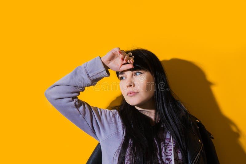 Portrait upset girl woman hood sunglasses background yellow sad grief sorrow brunette shadow sun light tropical leaves. Portrait of upset girl with hood on her stock photos