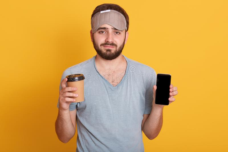 Portrait of upset handsome bearded young hipster man in gray t shirt and blindfold standing with coffee in one hand and phone with stock photos