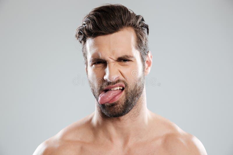 Portrait of an upset irritated naked bearded man showing tongue. Isolated over white background stock image