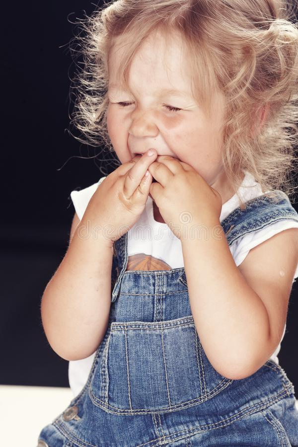 Portrait of an upset little girl in denim overalls, sitting in a studio on black background. royalty free stock image