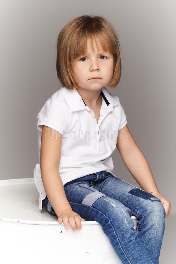 Portrait of an upset little girl in denim overalls, sitting in a studio on gray background. stock photo