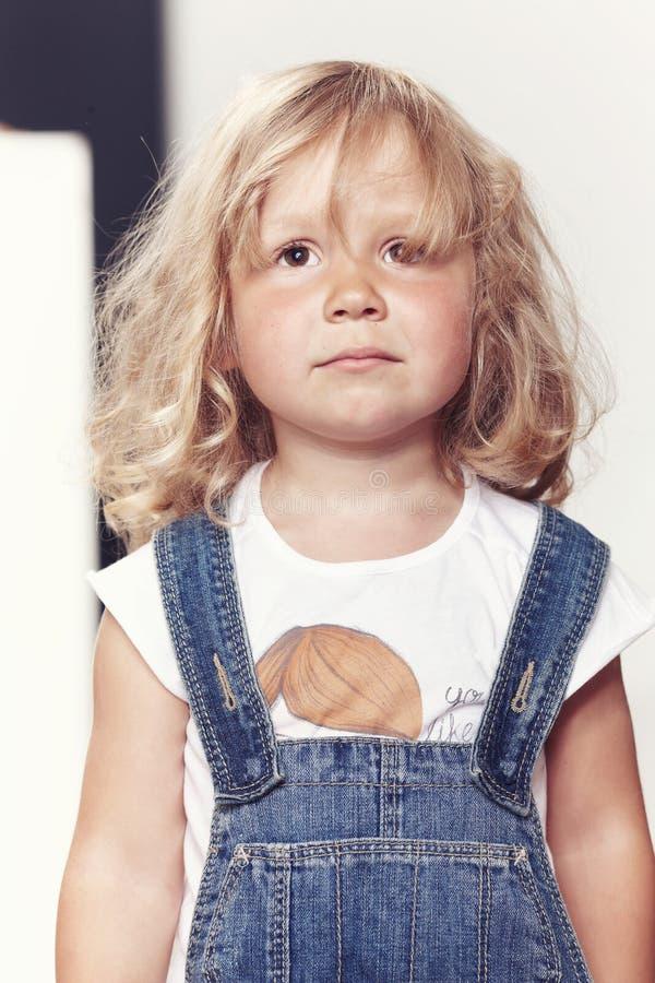 Portrait of an upset little girl in denim overalls, standing in studio. stock photos