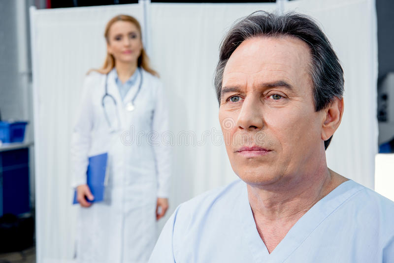 Portrait of upset middle aged patient with doctor behind royalty free stock photography