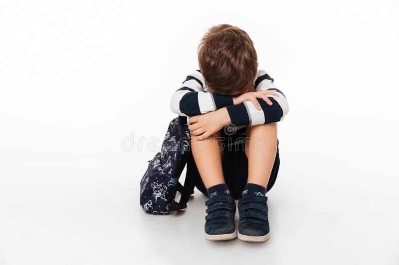 Portrait of an upset sad little kid with backpack royalty free stock photos