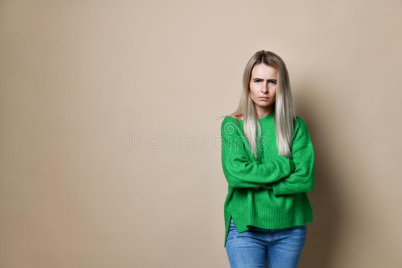 Portrait of an upset unsatisfied woman standing with arms folded and looking away. Over beige background royalty free stock images