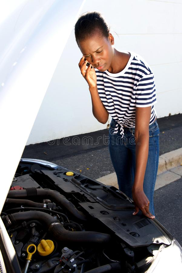 Upset young african woman standing by broken down car parked on the side of a road and calling for assistance royalty free stock photo